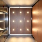 a photo from beneath a custom elevator ceiling with unique perimeter lights and veneer.