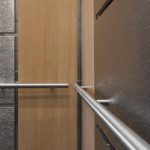 #Elevator Wall Panels faced with pattern stainless steel and formica laminate and a round stainless steel handrail