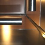 A GR602e elevator interior design looking upward, catching reflections of light from trim in between elevator wall panels and round stainless steel handrail.