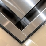 Glass observation cab ceiling corner joints atop glass wall panels