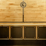 "Rear wall displays painted logo and border from fencing gym floor, reclaimed and encased within a black maple surround. The lower wall panels are ½"" rubber wainscot edged in brass binder angles and decorated with brass bolts and leather washers. The cars all feature bronze handrails with either a returned end (if near the door) or straight-end (at corners and near COP) and are supported by custom brackets affixed to the upper wall panels."