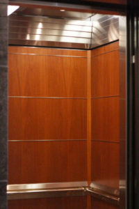This custom elevator incorporates solid hardwood (african mahogany), Mirror #8 stainless steel, custom etched entrance doors