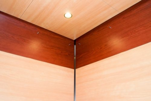 A close up of upper elevator wall panels and coordinating wood grain faced elevator ceiling EPIC Solution GR602e elevator interior design at Double Tree Hotel, St. Paul MN