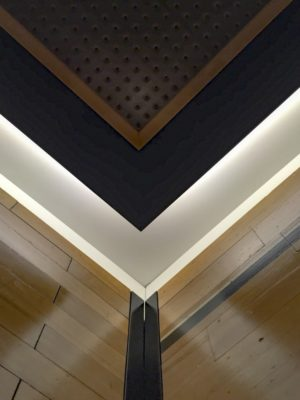Corner of elevator interior displaying suspended perforated painted steel (painted) ceiling, bronze trim, wood border and perimeter lights, reclaimed wood floors refurbished as upper elevator wall panels at Chicago Athletic Association Hotel CAA by G&R Custom Cabs