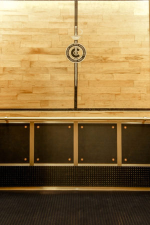 """Rear wall displays painted logo and border from fencing gym floor, reclaimed and encased within a black maple surround. The lower wall panels are ½"""" rubber wainscot edged in brass binder angles and decorated with brass bolts and leather washers. The cars all feature bronze handrails with either a returned end (if near the door) or straight-end (at corners and near COP) and are supported by custom brackets affixed to the upper wall panels."""