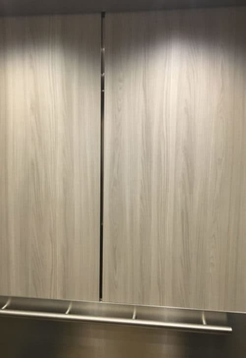 elevator wall panels of EPIC Solution #GR701e lower panel in 5WL and upper panel in plastic laminate. Showing round handrail.