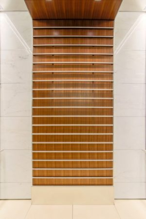 Beautiful and luxurious elevator cabins feature imported stone and quarter-sawn walnut veneer. Raised stainless steel bars decorate the rear walls.