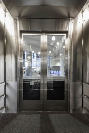 Front and rear opening glass elevator doors, large swing front with LED display screen and bar handrails, sidewalls are partially faced with 5WL patterned stainless steel.