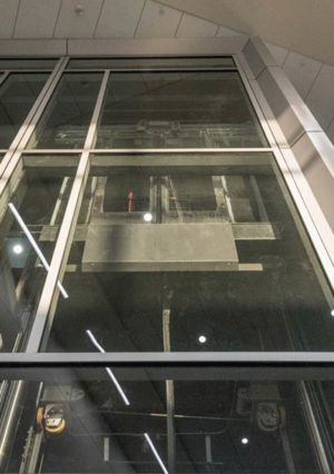 New Custom Elevator Cabs in Glass Elevator Shaft at MSP Airport A-G Concourse Connector, image displays shroud and external cabin components through glass elevator shaft.