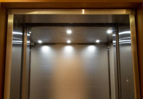 A close up photo of the elevator ceiling and entrances.