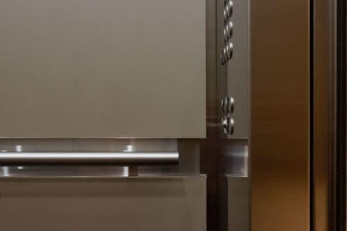 A closer view laminate wall panels, handrail channel, round handrail and car operating panel with buttons.