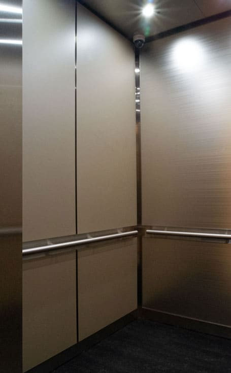 A close up photo of the sidewall of a custom elevator interior at 365 Nicollet, Minneapolis. Materials displayed are laminate, stainless steel and back-painted glass.